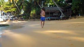 Barfota aktiva idrottsmankörningar på den gula sandiga stranden stock video