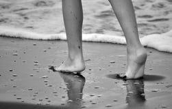 Barfota ben på stranden arkivfoto