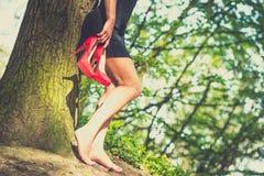 Barfota brunettflicka i den utomhus- svarta klänningen Arkivfoto