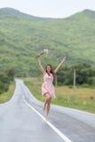 Barfota flicka med kamomillbukettspring längs vägen efter rommar royaltyfri bild