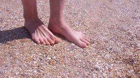 Barfota flickahandelsresande som masserar fot på den sandiga stranden i snäckskal på sjösidan lager videofilmer