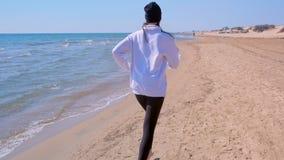 Barfota kvinna som tillbaka joggar på sport för sikt för havssandstrand körande utbildande stock video