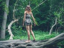 Barfota kvinnaanseende på ett stupat träd i skogen Arkivbild