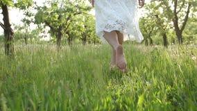 Barfota kvinnas ben som går på grönt gräs lager videofilmer