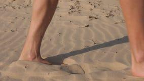 Barfota man som går på ökensandcloseupen Manlig skugga och fotspår på sand stock video