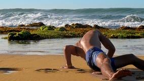 Barfota muskulösa gymnastövningar på gul våt sand arkivfilmer