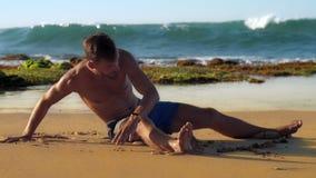 Barfota muskulösa manövningar på den sandiga stranden mot havet stock video
