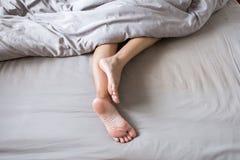 Barfota och ben under filten på sängen, når att ha vaknat upp i morgon arkivfoton