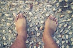 Barfota på cementstenspåret för den massagen sular av foten Arkivbild