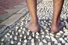 Barfota på cementstenspåret för den massagen sular av foten från baksida Arkivfoto