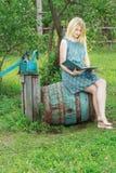 Barfota studentflicka i blå siden- kvinnlig klänningläsebok Arkivbilder
