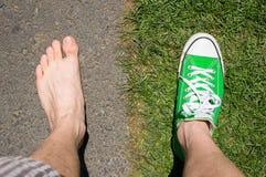 Barfuß gegen tragendes Turnschuhgras gegen Asphalt Lizenzfreie Stockbilder