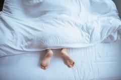 Barfuß und Bein unter Decke auf dem Bett stockbilder