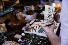BARGA ITALIEN - OKTOBER 8, 2017: Man som rymmer tappninghumorboken på loppmarknad i liten forntida medeltida touristic italiensk  royaltyfria bilder