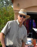 Bargain Hunting at Garage Sale. Mature man pauses in his shopping to look toward the camera. He is garage saling and is wearing a straw hat, sunglasses and plaid royalty free stock photos