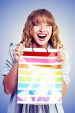 Bargain shopping woman laughing with joy. While holding a colourful striped carrier bag with purchases bought at low prices with huge savings Stock Images