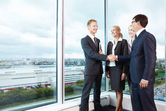 Bargaining. Two businessmen shake hands next to business women Stock Photography