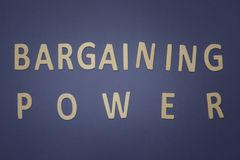 Bargaining Power written with wooden letters on a blue backgroun. D to mean a business concept Stock Photos