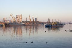Barge and building cranes on river channel royalty free stock photo