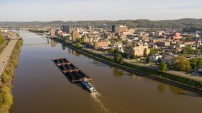 Barge Carries Coal Along Kanawha River and Charleston West Virgina. Charleston West Virgina ia an active seaport here a barge moves coal around stock images