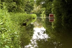 Barge on Chesterfield canal. Red barge amongst lush green foliage reflected on the Chesterfield canal in Derbyshire Stock Photos