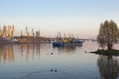 Barge and construction cranes on a river royalty free stock photo