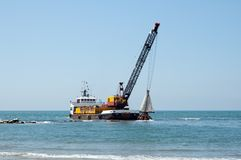 Barge dredging a harbor. A barge is dredging a harbor removing stones and sand Royalty Free Stock Photo