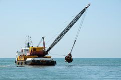 Barge dredging a harbor. A barge is dredging a harbor removing stones and sand Royalty Free Stock Photos