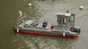 Barge floating on river with trash can and scoop net aboard, municipal service. Stock footage stock video footage