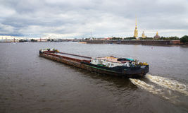 Barge floats on the Neva against the background of the fortress. Stock Image