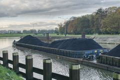 The barge flows along the river, transports coal to the power plant, repairing water routes, and green transport royalty free stock images