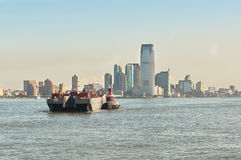 Barge in front of Manhattan, New York. Manhattan,New York,USA - June 27, 2011 : Barge towed by a tugboat on Hudson River stock image