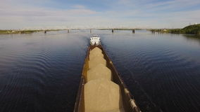 Barge loaded with sand and gravel floats on the wide river on the background of the bridge. Aerial view stock footage
