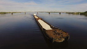Barge loaded with sand and gravel floats on the wide river on the background of the bridge. Aerial view stock video