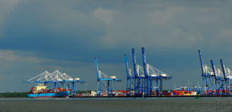 Barge and loading cranes. Cranes loading cargo onto barges Royalty Free Stock Images