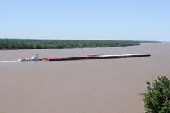 Barge at Mississippi River. Tugboat moves barge on muddy Mississippi river stock photos