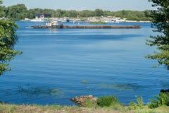 Barge mit Fracht auf Fluss, Ansicht vom Ufer Stockfoto