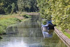 A barge moored to the bank on the Grand Union Canal at Lapworth in Warwickshire, England stock images