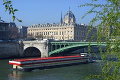 Barge on Paris River. Barge floats down river in Paris pass Conciergerie in background Royalty Free Stock Photography