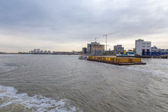 Barge pulling a load of containers downriver at Woolwich, London Stock Images