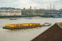 Barge pulling yellow containers on the River Thames at Greenwich Royalty Free Stock Photo