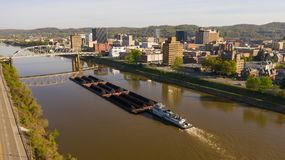 Barge Pushes Resources Down the River in Front of Charleston West Virginia. The Kanawha River carries shipping traffic exported from Charleston West Virginia stock photography