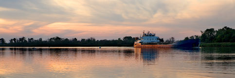 Barge on river. Panoramic view of barge sailing on river at sunset Royalty Free Stock Photos