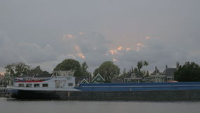 Barge sailing by the village houses stock video footage