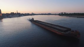 Barge sails along the river near the city port on sunset aerial footage. 4K UHD stock video footage