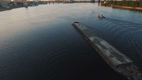 Barge sails along the river near the city port on sunset aerial footage. 4K UHD stock footage