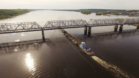 Barge with sand and gravel sails under the railroad bridge across the river. Aerial view stock footage