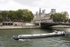 Barge and Tugboat cargo ship sailing in Seine river near Hotel de Ville royalty free stock photos