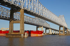 Barge Under Bridge. Large red transportation ship passes under the Crescent Connection Bridge on the Mississippi River in New Orleans, Louisiana Stock Images
