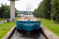 Barge with wood. Barge with wood passes through a sluice in Finland Royalty Free Stock Photo